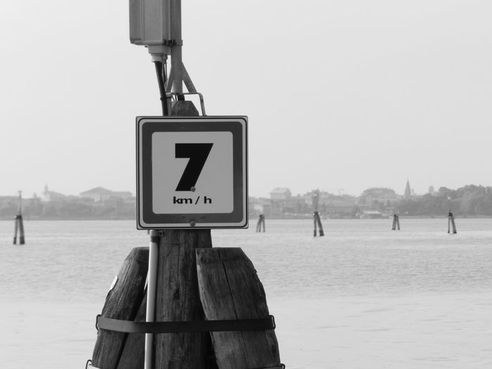 Information sign on wooden post by sea against sky