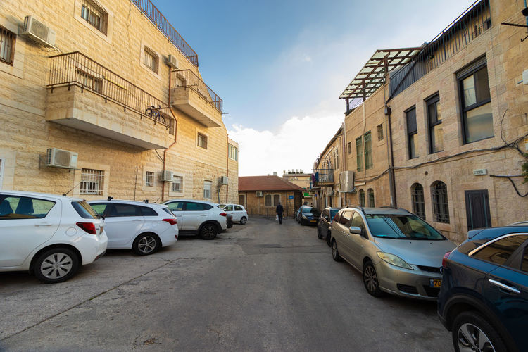 Cars parked on road by buildings against sky