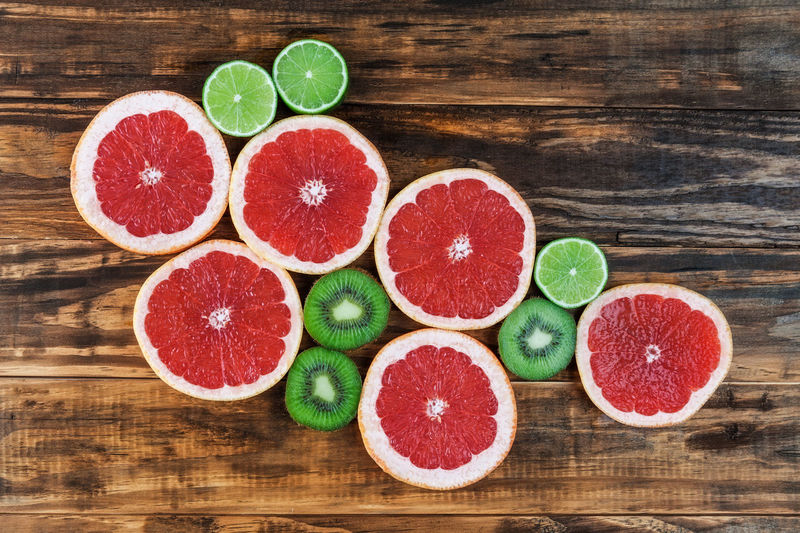 Slices of red grapefruit, lime, and kiwi arranged on rustic wooden table. Top view with copy space Blood Orange Citrus Fruit Close-up Cross Section Day Food Food And Drink Freshness Fruit Grapefruit Healthy Eating Indoors  Large Group Of Objects Lime Multi Colored No People SLICE Variation