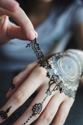 Midsection of woman removing henna tattoo from hand