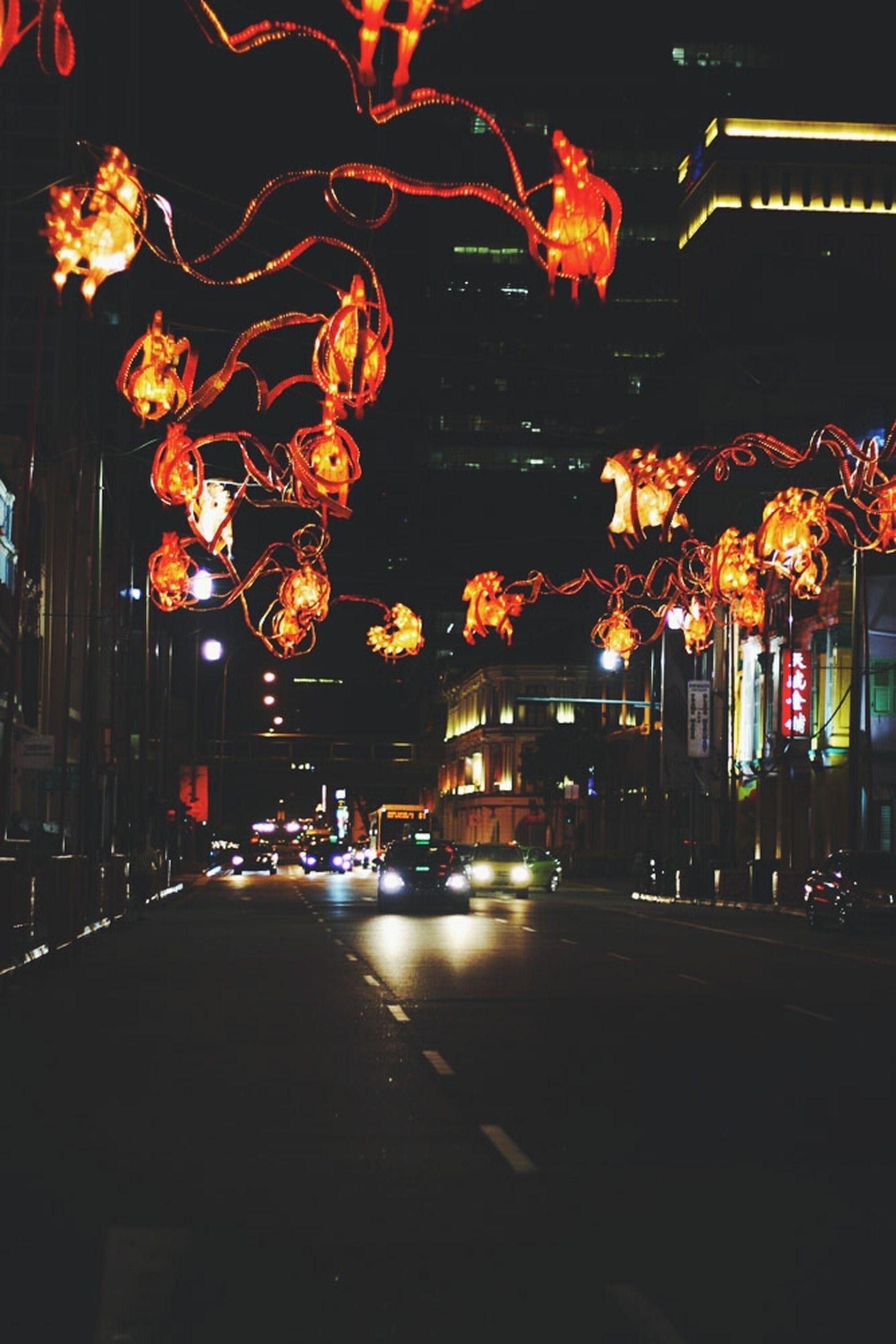 night, illuminated, street, lighting equipment, building exterior, street light, built structure, city, architecture, road, transportation, light - natural phenomenon, outdoors, incidental people, decoration, tree, city life, dark, glowing, no people