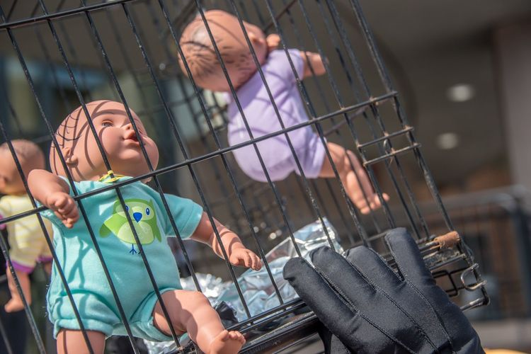 Protester holds caged babies in protest of immigration policies. Glove Hand Immigration Protest Immigration Protests Dolls Protest Crate EyeEm Selects Cage Focus On Foreground Metal