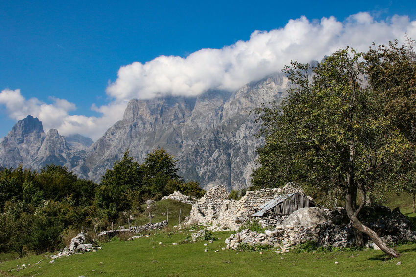 Albanian Alps near Valbone Albanian Alps Architecture Beauty In Nature Building Exterior Built Structure Cloud - Sky Clouds Day Grass Landscape Mountain Mountain Range Nature No People Old Ruin Outdoors Scenics Sky Tranquil Scene Tree