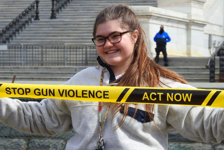Student protester at the National School Walkout on the National Mall in front of the US Capitol building, Washington, DC, to demand political action to address gun violence on March 14, 2018. Activists National School Walk Out US Capitol Building Activism Adult Close-up Cordon Tape Crime Crime Scene Day Gun Control Gun Violence Happiness High School Students Looking At Camera One Person Outdoors People Portrait Protesters Real People Smiling Yellow Young Adult