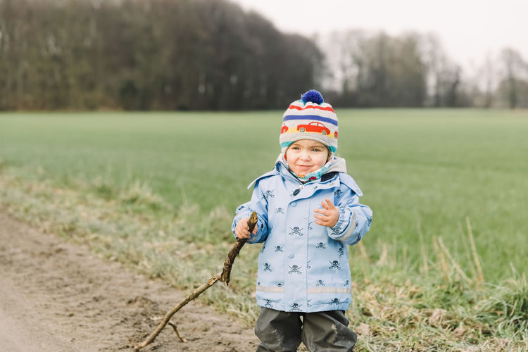 Cute boy holding tree stick standing on field