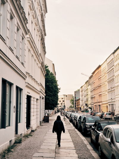 Rear view of man walking on street amidst buildings in city