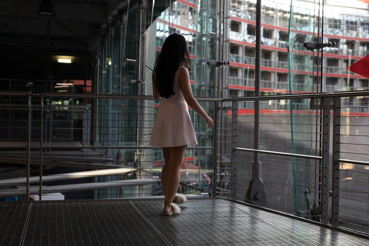 Rear View Of Woman Walking On Floor By Railings