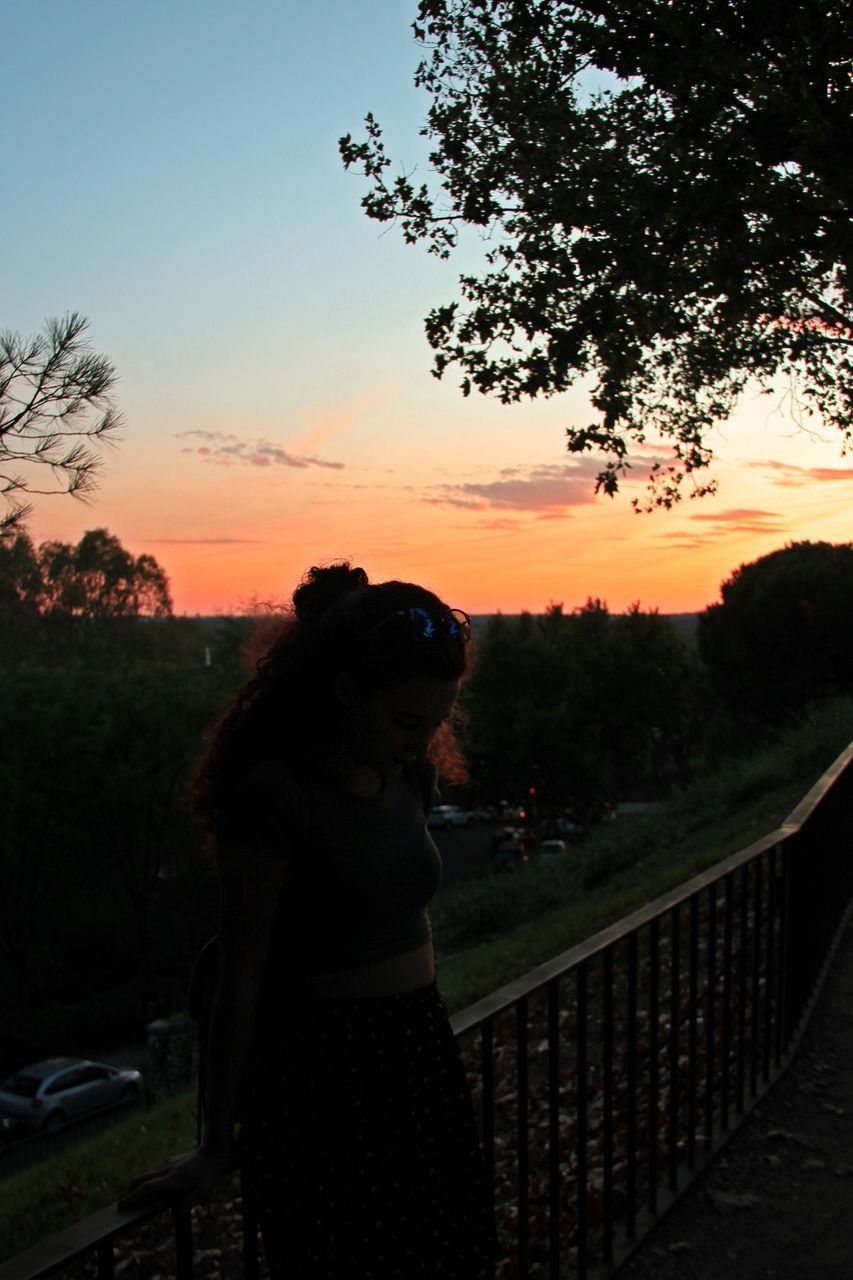 sunset, tree, sky, railing, outdoors, silhouette, nature, standing, one person, scenics, beauty in nature, real people, clear sky, day, people
