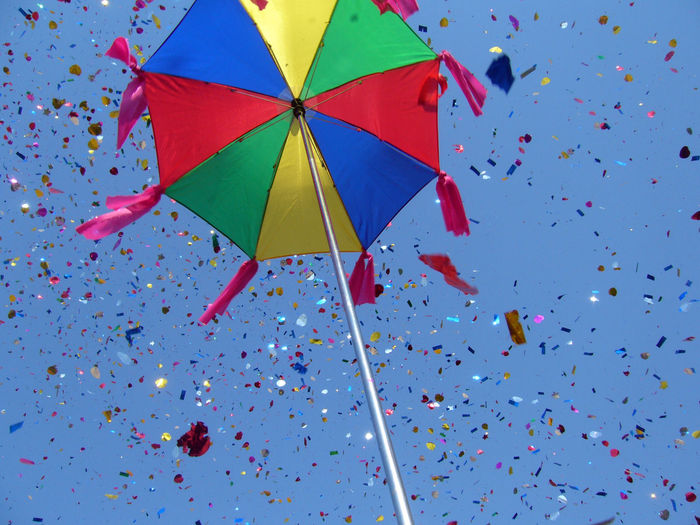 Low Angle View Of Confetti Falling From Colorful Umbrella Against Sky