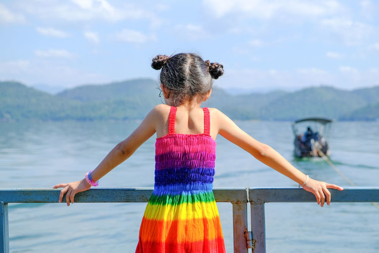 Adult Beauty In Nature Childhood Day Focus On Foreground Hairstyle Human Arm Leisure Activity Lifestyles Nature One Person Outdoors Real People Rear View Scenics - Nature Sea Standing Three Quarter Length Water Women