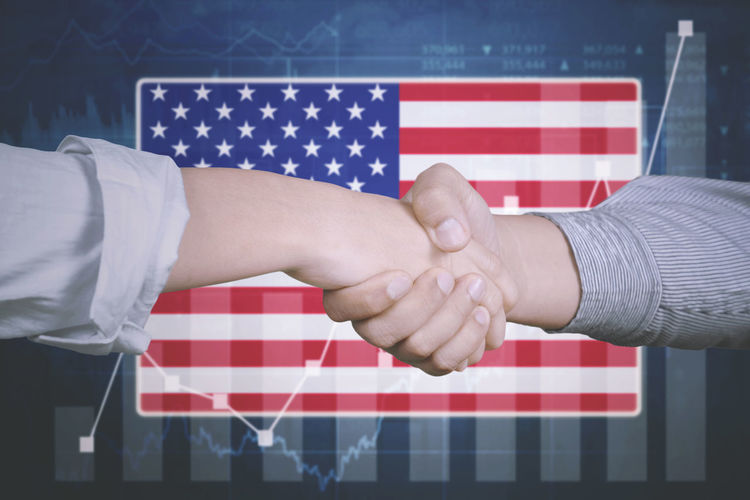 Cropped Image Of People Shaking Hands Against American Flag