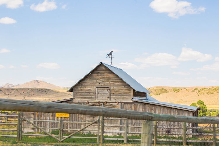 Rustic farm building in rural, midwestern landscape. Farm Farm Life Farmer Farmland Architecture Belief Building Building Exterior Built Structure Cloud - Sky Day Environment Farm House Field Landscape Mountain Nature No People Outdoors Place Of Worship Religion Rural Scene Sky Spirituality Wood - Material