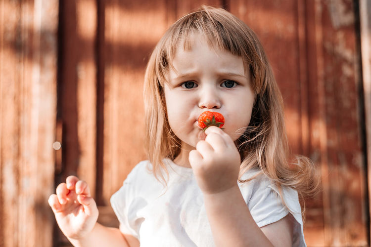 Portrait of cute girl eating strawberry