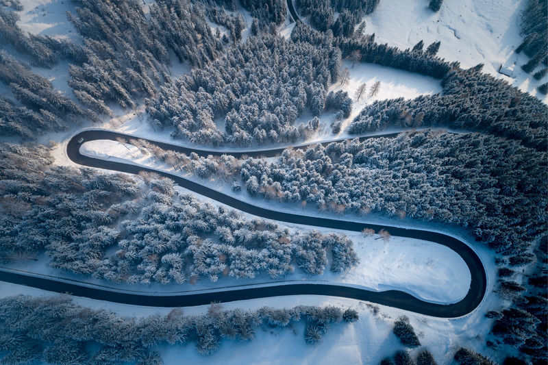 Aerial view of winding road amidst trees during winter