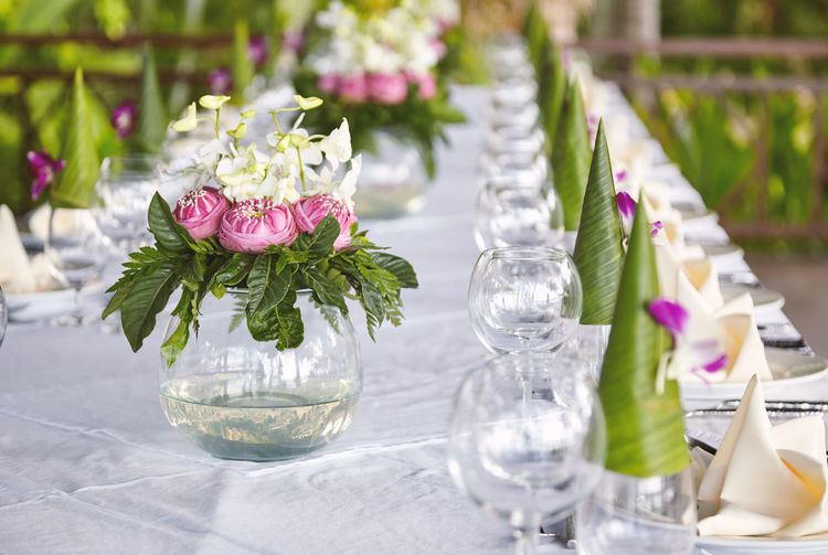 The circle shape glass vase of pink flowers and green leave bouquet decoration on the white cover dinner table for wedding reception dinner celebration Reception Wedding Arrangement Beauty In Nature Bouquet Day Decoration Drinking Glass Flower Flower Arrangement Flower Head Flowering Plant Fragility Freshness Glass Glass - Material Nature No People Outdoors Place Setting Plant Setting Table Tablecloth Vase