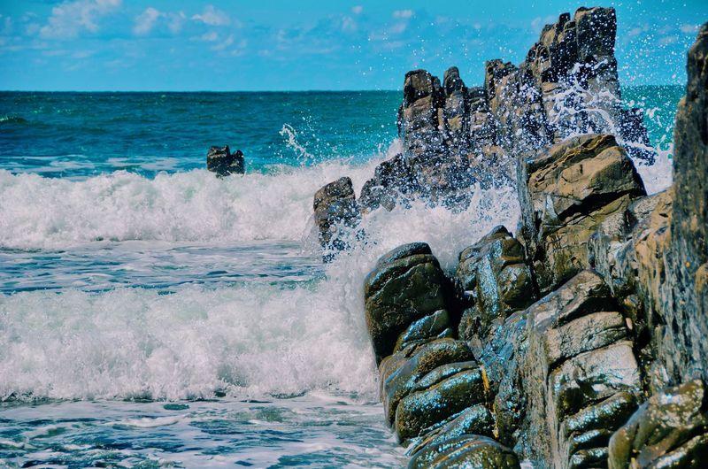 Water splashing on rocks at sea shore against sky