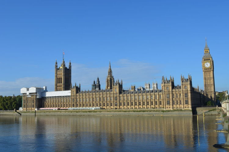 Big ben and houses of parliament by thames river against blue sky