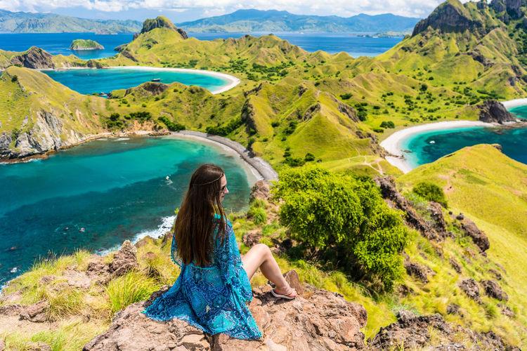 Woman sitting on rock against sea