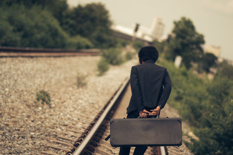Businessman with suitcase walking on railroad track