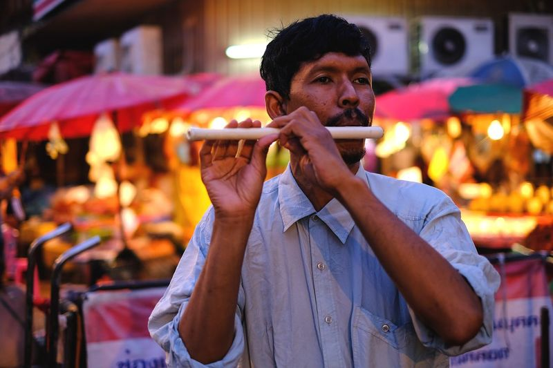 Close-up of man playing flute while standing in market