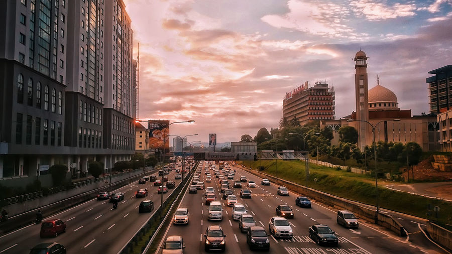 Traffic on road amidst buildings in city against sky