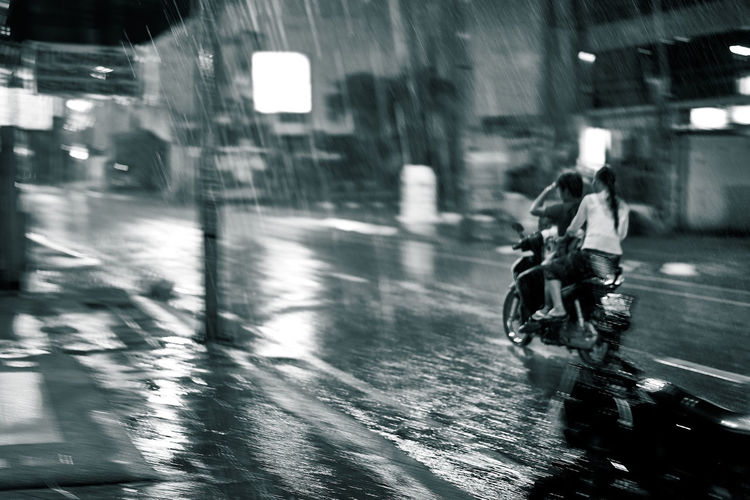 Riding a Motorbike in the Rain Blackandwhite Blurred Motion Boy Bright Lights City Life City Street Dreamlike Family Glistening Holding Illuminated Mode Of Transport Motion Motorbike Movment On The Move Outdoors Reflections Riding Shimmering Speed Street Transportation Woman
