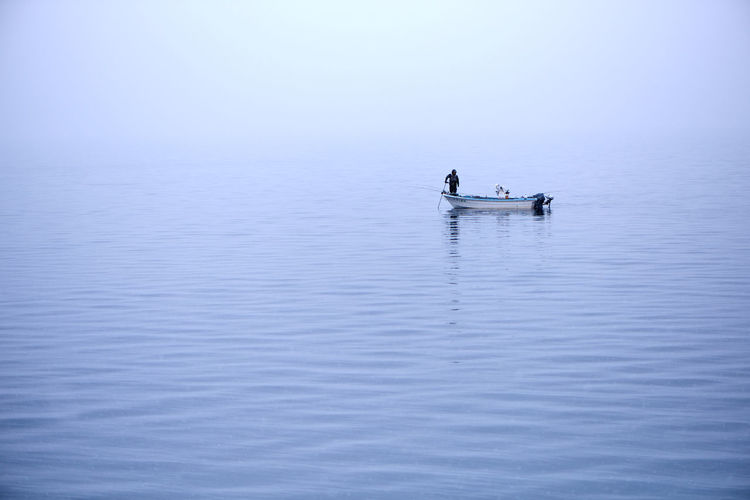 A lone man fishes from a small and simple boat on a lake in Hokkaido - Japan's frozen north. With temperatures at 20 degrees below freezing, only the high sulphur content and astounding depth of this volcanic lake stops it from freezing over. Alone Time Beauty In Nature Boat Fishing Idyllic Lake Minimalism Nature Reflection Scenics Snow Tranquil Scene Tranquility Water Been There. Lost In The Landscape