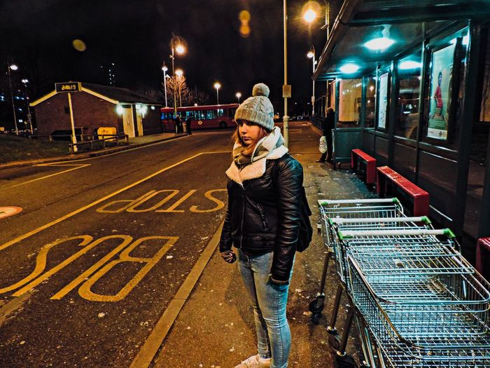 Young woman in warm clothing standing on sidewalk at night