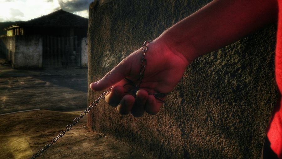 Cropped image of man holding chain by wall