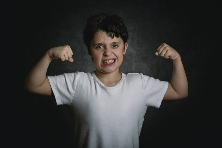Portrait of smiling boy flexing muscles while standing against black background