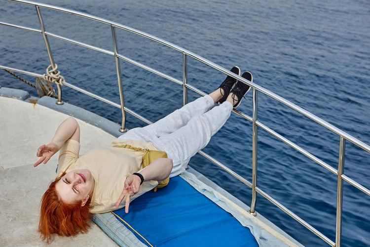 Woman lying on boat in sea
