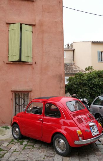 Red vintage car outside building