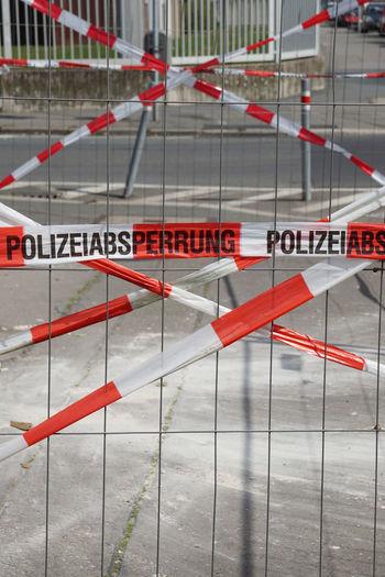 Cordon tape behind fence on street