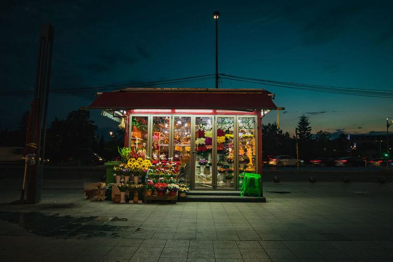 Illuminated street market against sky at night