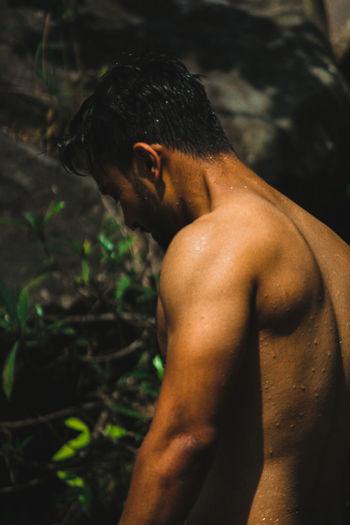 Shirtless wet muscular man standing outdoors
