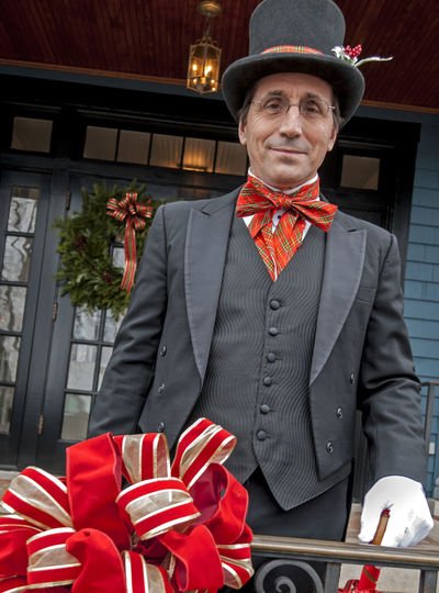 Low Angle Portrait View Of Mature Man In Top Hat Outside House During Christmas
