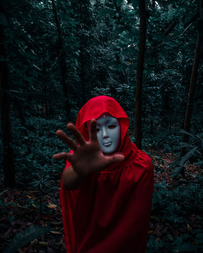 Portrait of man wearing mask while standing by trees in forest