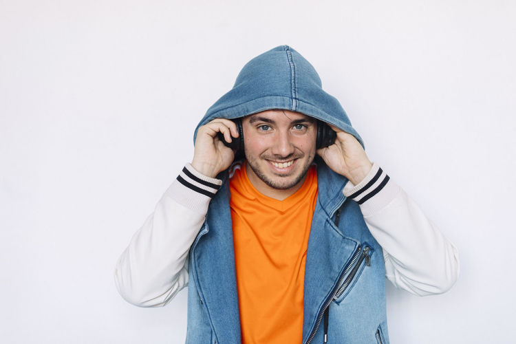 Portrait Fashionable Young Man Standing Headphones Hoodie Hair Lifestyle Smiling Adult Looking Camera Modern Attractive person One Bearded Style Confident  Male White Beard Personality  Youth Studio Handsome People Single Hipster Posing Cool Background Fun Emotion Happy Fashion Expression Long Mature Casual Stylish Caucasian Guy Earphones Earbuds Listening Music One Person Front View Clothing Indoors  Young Adult Young Men