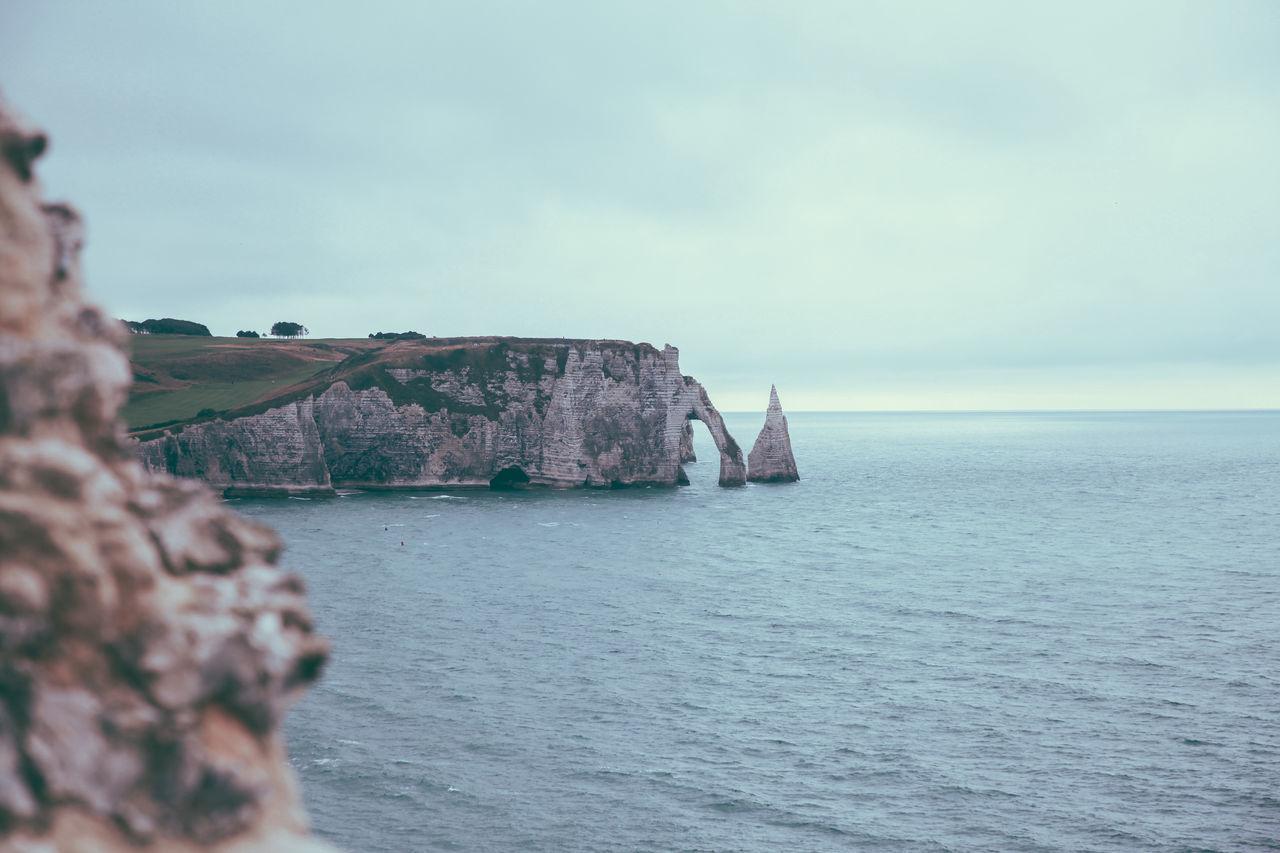 Cliff on sea against cloudy sky