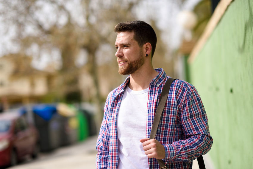 Young bearded man walking in urban background. Traveler wearing casual clothes. Lifestyle concept. Beard Button Down Shirt Casual Clothing Contemplation Day Focus On Foreground Front View Fully Unbuttoned Leisure Activity Lifestyles Looking Looking Away Men One Person Outdoors Portrait Real People Standing Waist Up Young Adult Young Men