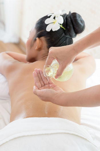 Cropped image of therapist pouring massage oil on woman lying at health spa