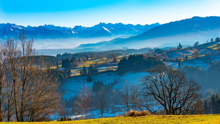 Scenic view of landscape and mountains against blue sky