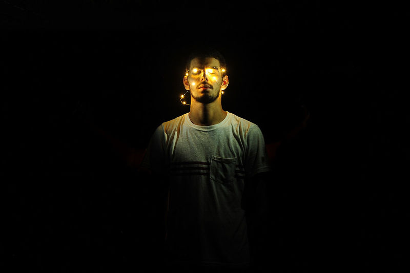 Man standing with illuminated string lights against black background