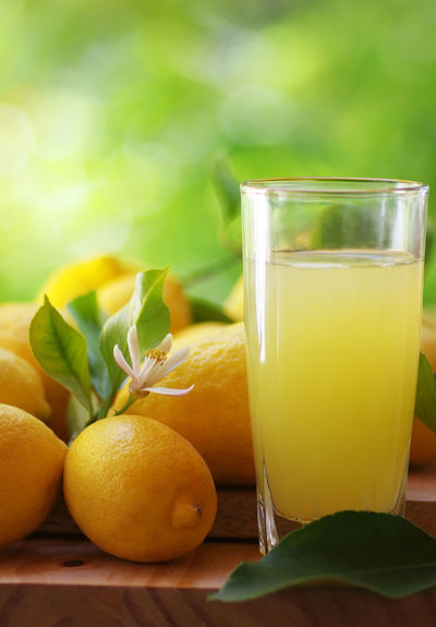 ripe lemons and juice cup on table Cup On Table Citrus Fruit Close-up Drink Drinking Glass Food Food And Drink Freshness Fruit Glass Green Color Healthy Eating Juice Fruit Leaf Plant Part Refreshment Ripe Ripe Lemons Table Wellbeing