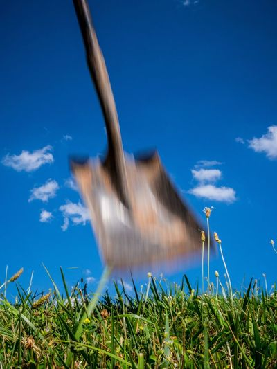 Blurred motion of shovel over field against blue sky