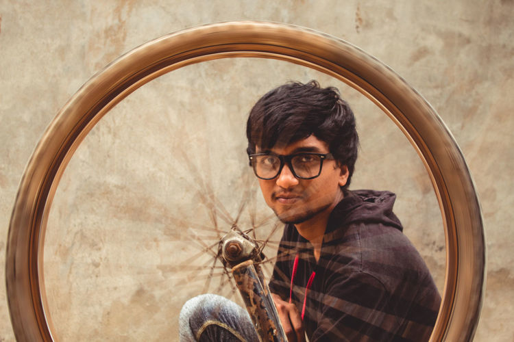 Portrait Of Young Man Repairing Bicycle