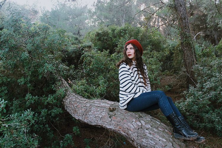 Woman Sitting On Tree In Forest