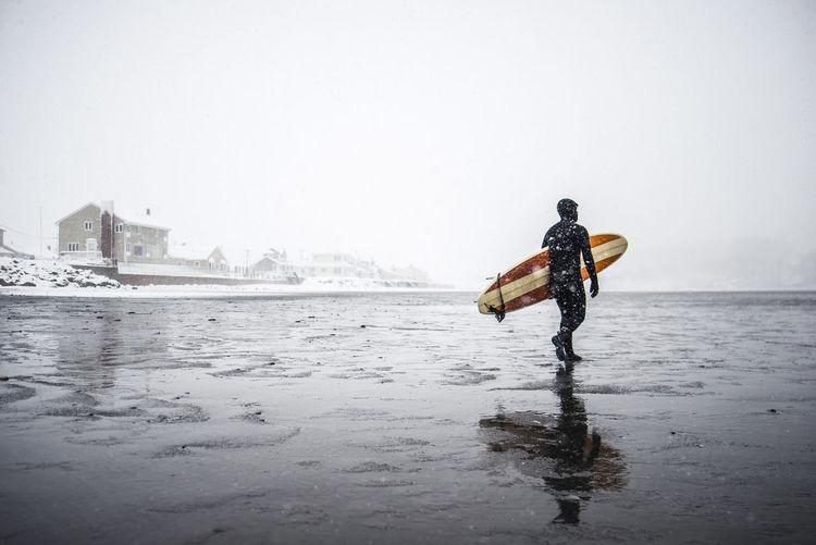 Man on snow covered sea against clear sky