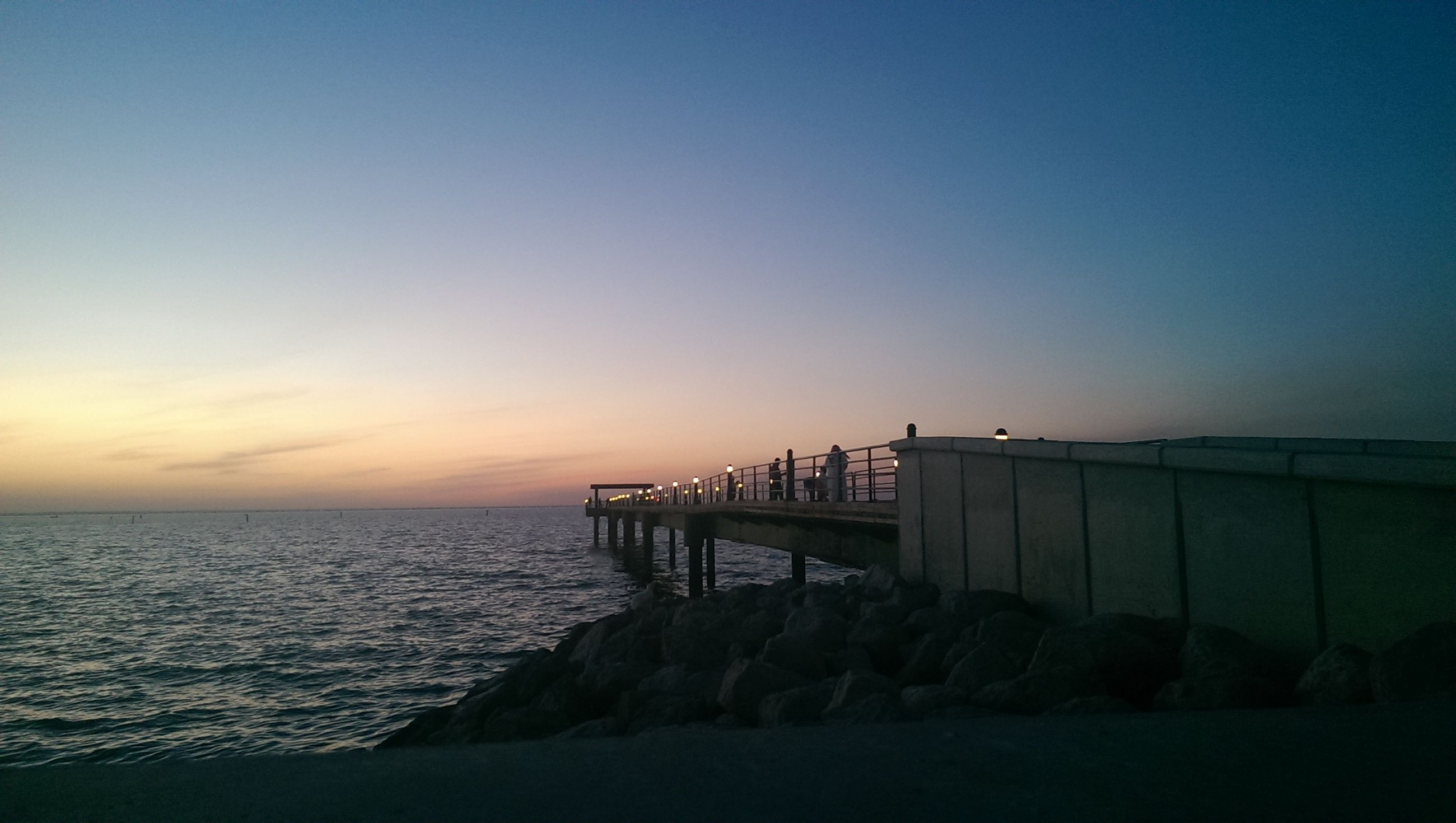 sea, water, horizon over water, scenics, copy space, tranquil scene, tranquility, clear sky, beauty in nature, pier, sunset, built structure, beach, nature, sky, idyllic, shore, rock - object, architecture, blue