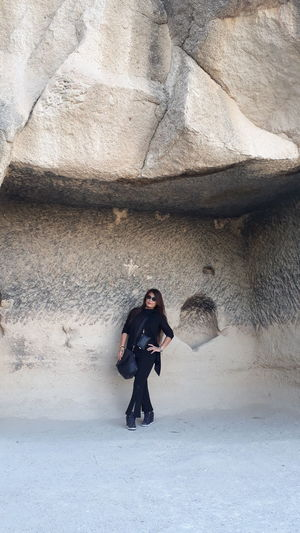 Full length of woman standing by rock formation